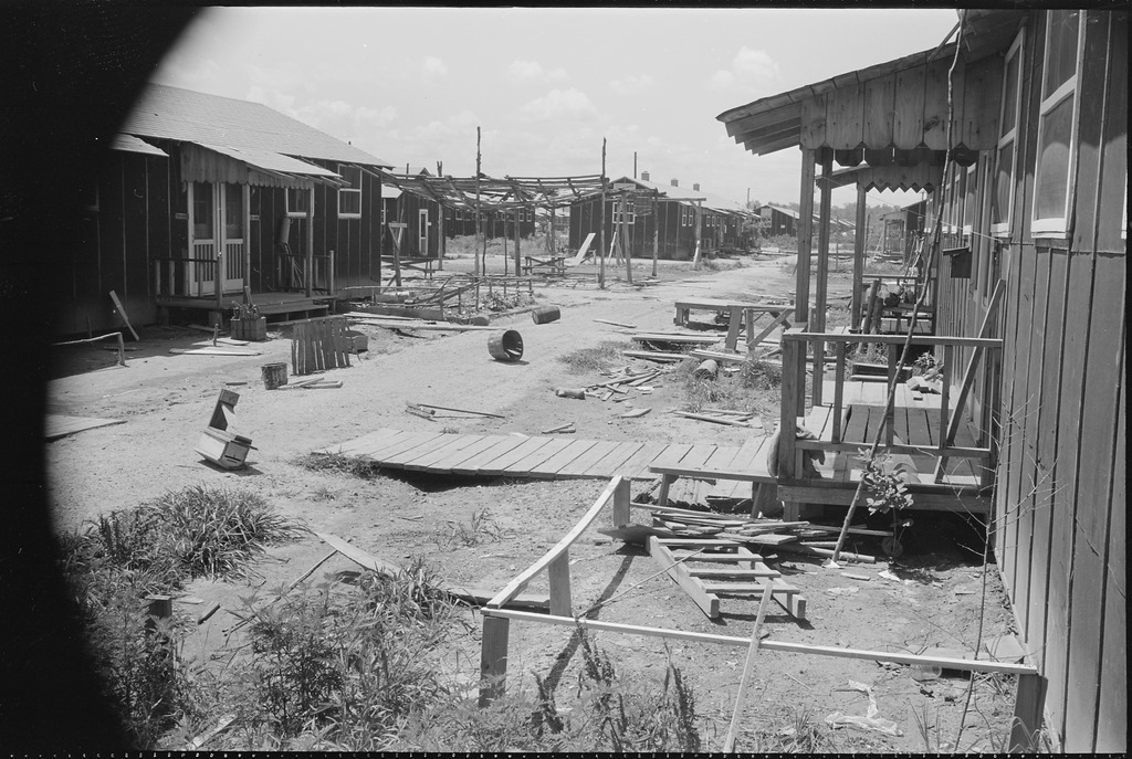 An empty block of barracks with lumber strewn on the ground in Jerome after closing.